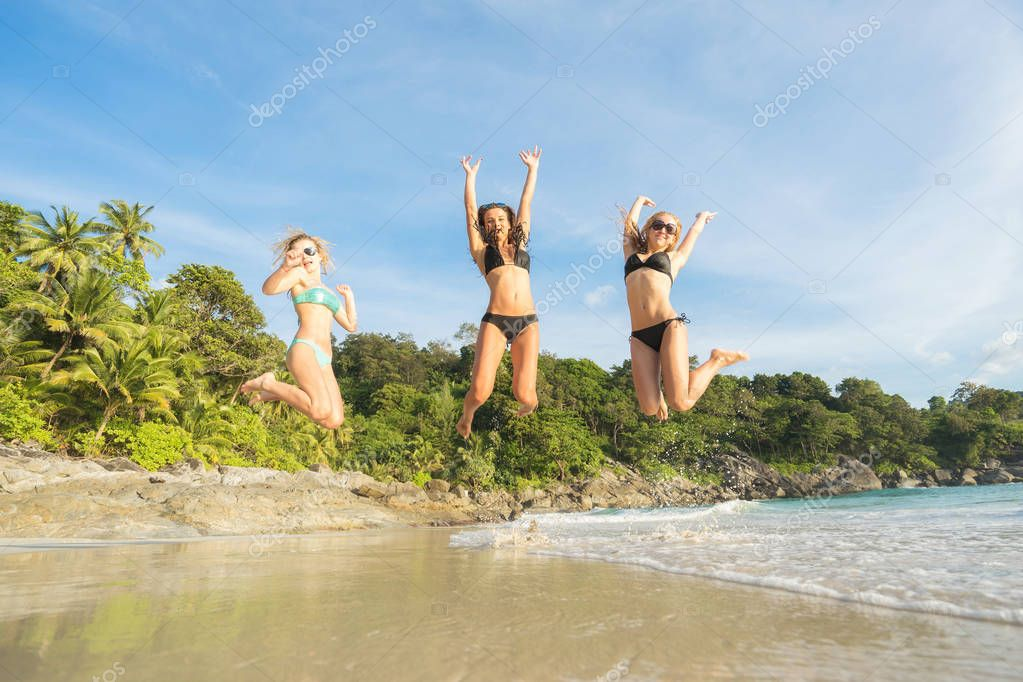 happy girls jumping on the beach.