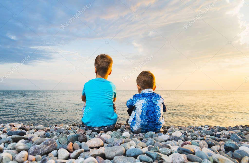children sitting on the beach
