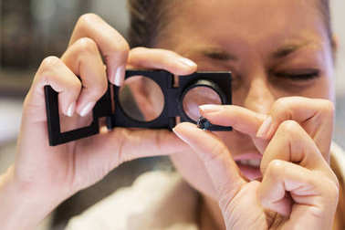 Jeweler looking at stone through loupe