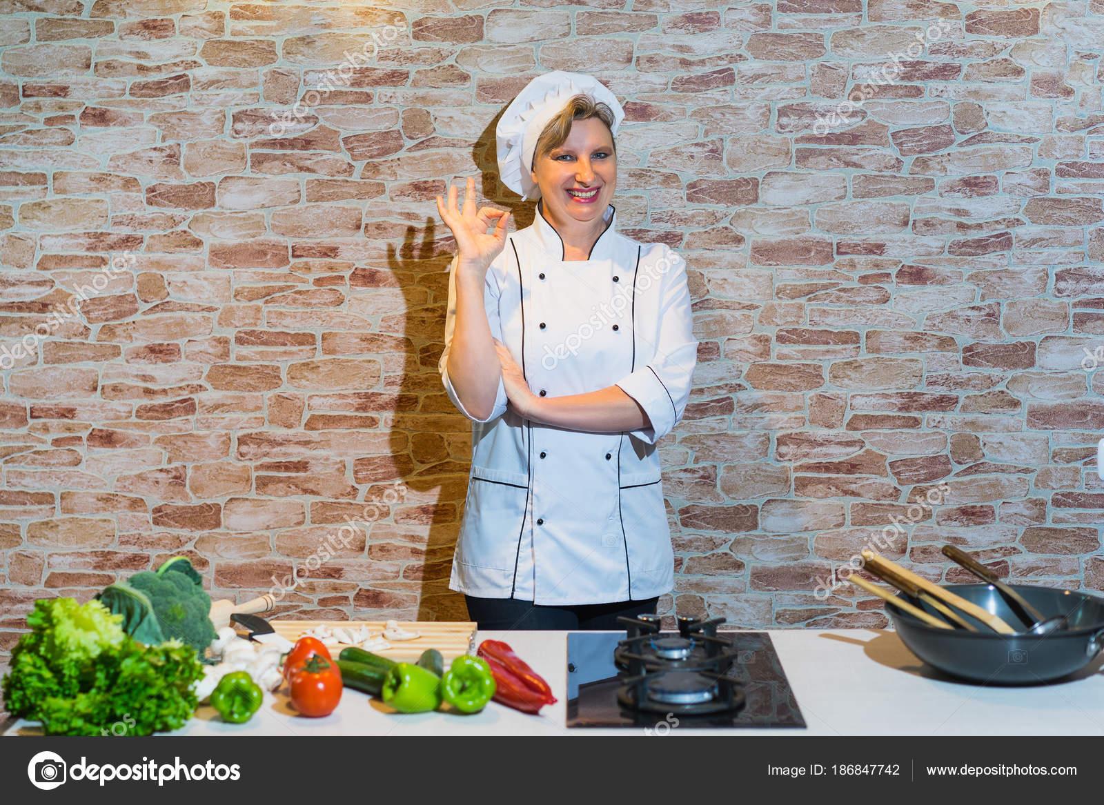 Glückliche Frau Zeigt Koch Einheitlich Auf Die Küche Mit Gemüse ...