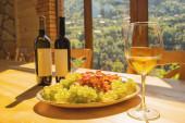 Láhve od vína, hrozny a sklenice vína na dřevěném stole s horami v oknech jasné pozadí. Selektivní zaměření.