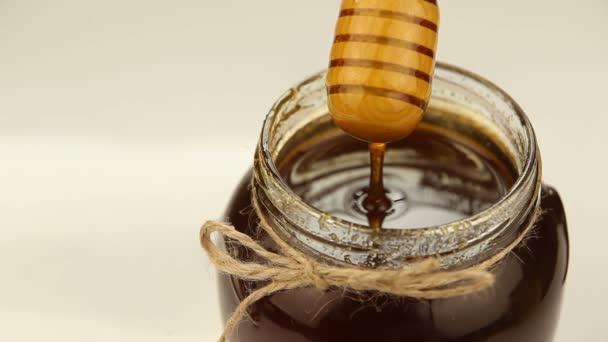 Delicious delicious honey in  jar on table