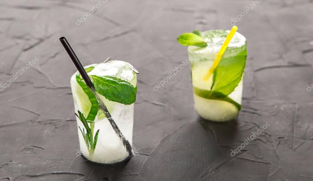 two glasses with fresh cocktail made of ice on concrete table
