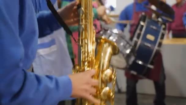 Hudebník, vášnivě hrál na saxofon v pozadí s bubeníky