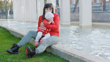 Happy mother sitting with baby in her arms near fountain and having fun