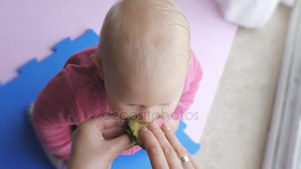 Dítě jíst avokádo z rukou matky.