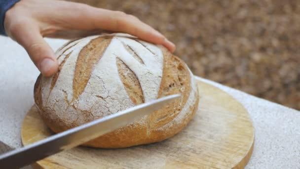 Mens hands cut a loaf of bread