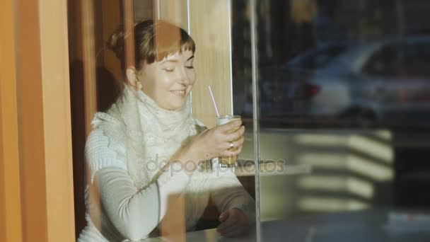 Young woman drinks coffee in cafe. Portrait of caucasian woman with lace wool scarf smiling and sipping latte through a straw behind a window