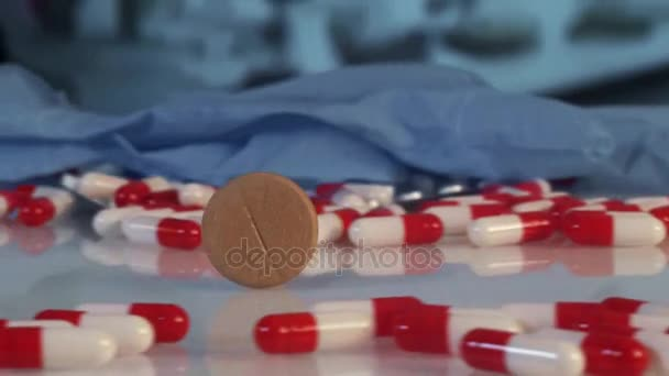 tablet rolls among medicines and pills over white background