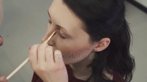Maskérka aplikuje oční stíny. Krásná žena tvář. Dokonalý make-up. Rty. Kosmetické oční stíny. Make-up detail