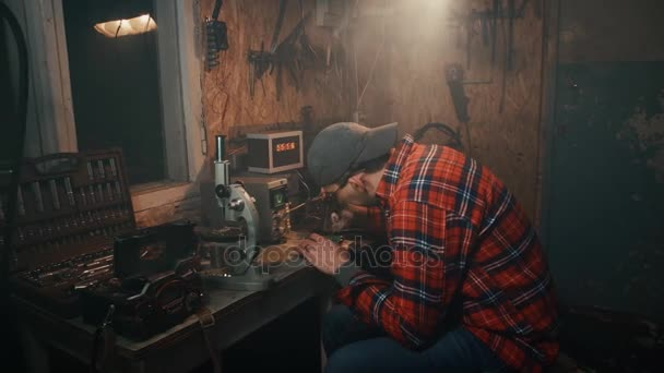 der Mann in der Garage ist mit dem Löten beschäftigt
