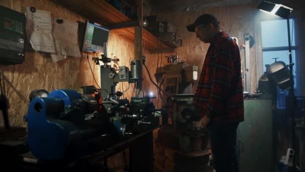 mužské hlavní inženýr řídí cnc vrtací stroj v garáži tmavá dílna