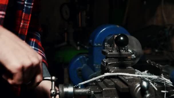 Männlicher Meister bei der Arbeit an einer alten Drehmaschine in einer dunklen Werkstatt in Großaufnahme