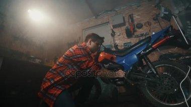 a man is repairing a motorcycle in a dark garage