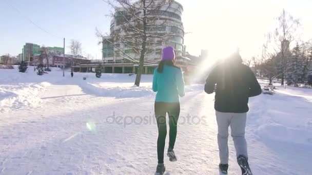 girl and guy jogging on a sunny day in winter in background of the cityscape