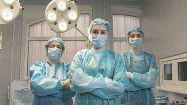 three girls nurse in the operating room take off the face mask and smile