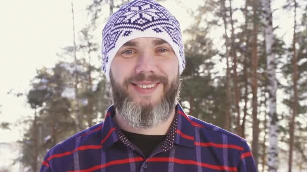 portrét vousatého usmívajícího se muže v zimním lese