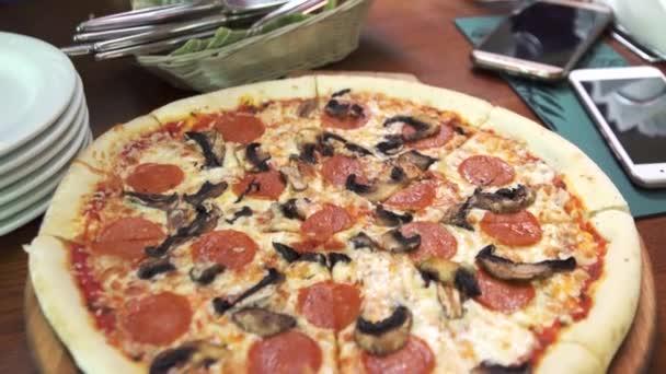 Pizza s žampiony nakrájíme na kousky
