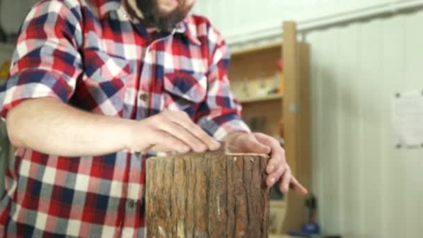 carpenter muž v košili leštění pařez v dílně
