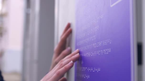 blind girl on the street reading a braille font on a building sign