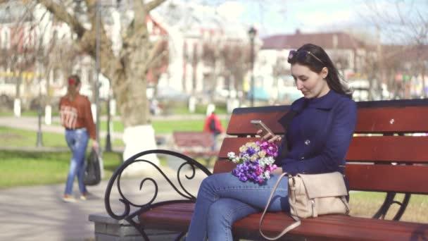 süße Mädchen im Frühlingspark genießt die Telefon Lächeln