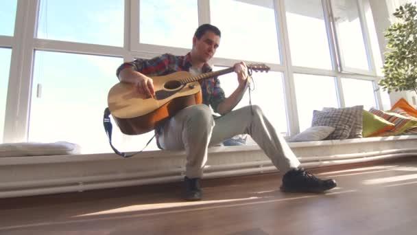 muž v košili hraje akustickou kytaru v prosluněné místnosti