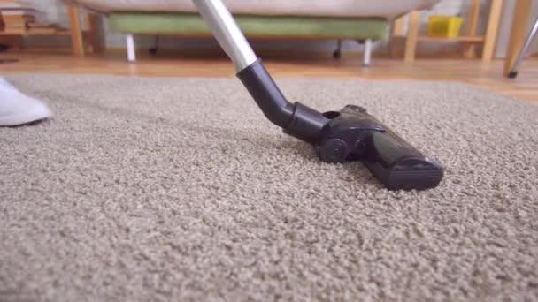 junge Frau benutzt Staubsauger beim Teppichputzen im Haus aus nächster Nähe