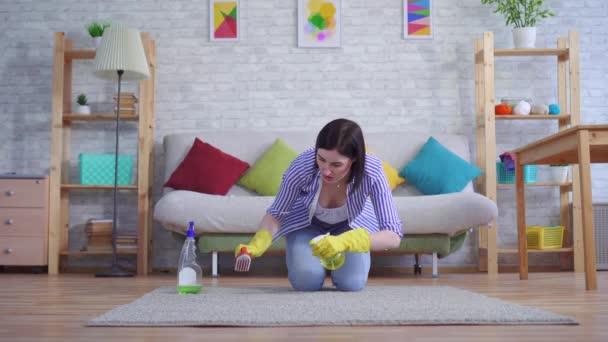 junge Frau in Handschuhen mit Unzufriedenheit reinigt den Teppich mit ihren Händen