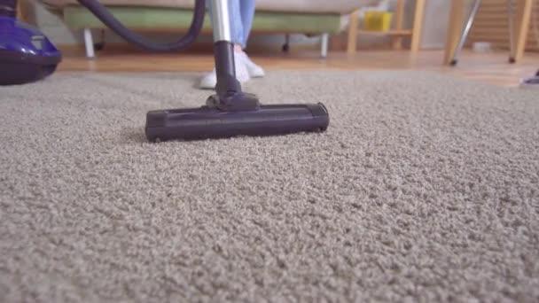 junge Frau benutzt Staubsauger beim Teppichputzen im Haus