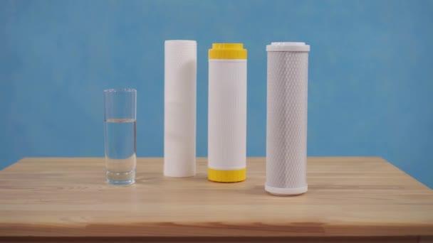 Tiszta vízszűrő patron és tiszta víz üvegben