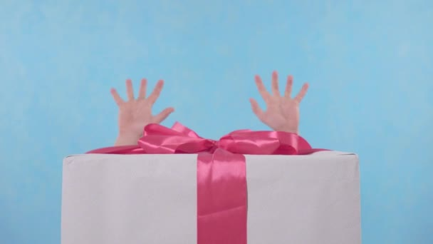 srandovní šťastný muž s knírem se dívá zpoza velkého dárku na modrém pozadí