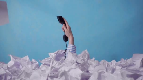 hand holding the phone reaches out from a large heaps of crumpled paper