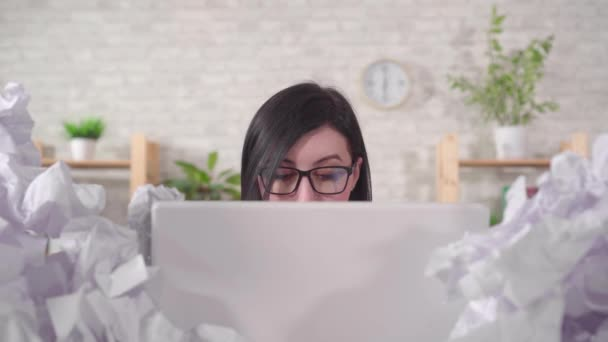 woman office worker with glasses is working at a laptop in a heaps of paper on an office desk
