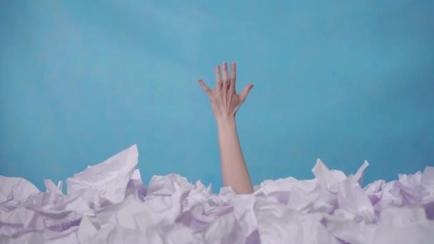 Hand reicht aus einem großen Haufen zerknüllten Papiers