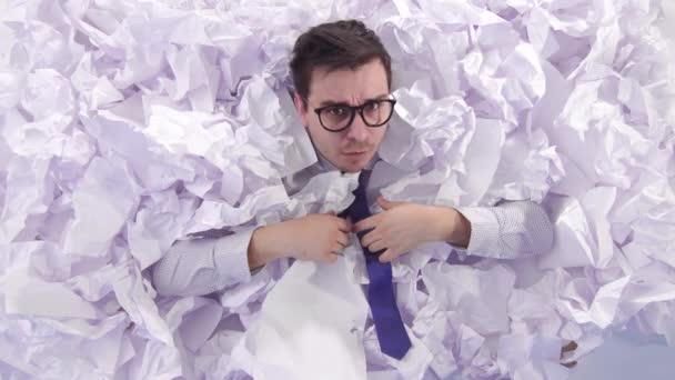 ehrfürchtiger Mann Büroangestellter mit Brille in einem großen Haufen zerknülltem Papier