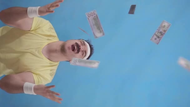 Funny young mustachioed man from the 80s catches flying paper money standing on a blue background vertical video slow mo