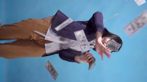young business woman scatters throws paper money on a blue background of a vertical video slow mo