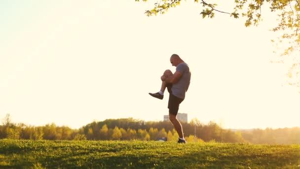mladý sportovní běžec dělá protahovací cvičení, příprava na cvičení v parku. Západ slunce, tónovaný, video