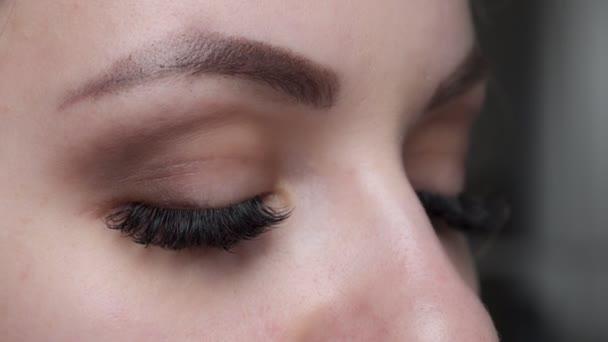 Postup prodloužení řas. Žena oko s dlouhé modré řasy. Ombre efekt. Zblizka, Selektivní ostření.