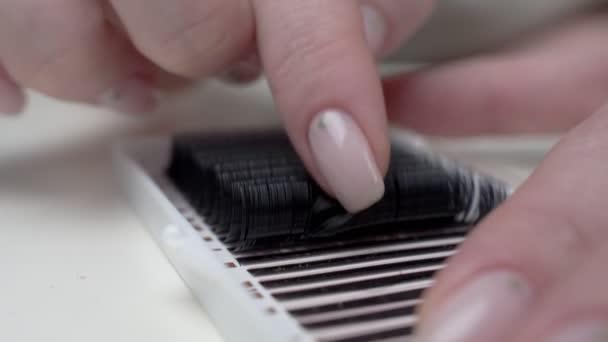Wimpernverlängerung. Nahaufnahme eines Meisters bei der Arbeit künstliche Wimpernverlängerungen Material. Hände des Meisters zeigen dicke Wimpern