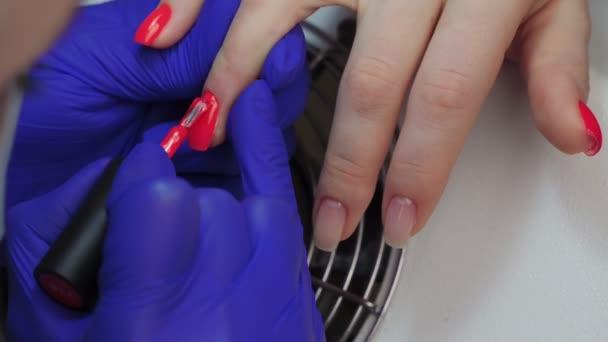 Nahaufnahme von professionellen Kosmetikerin Maniküre Meister Nagellack. Frau bekommt Nagelmaniküre. Die Nägel mit rotem Lack überziehen. Nagelpflege im Schönheitssalon.