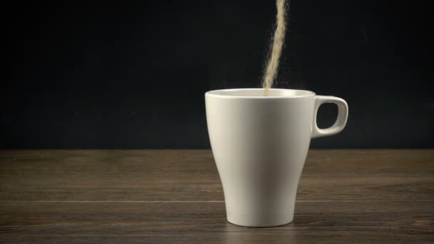 Instant coffee pouring into a white cup in slow motion.