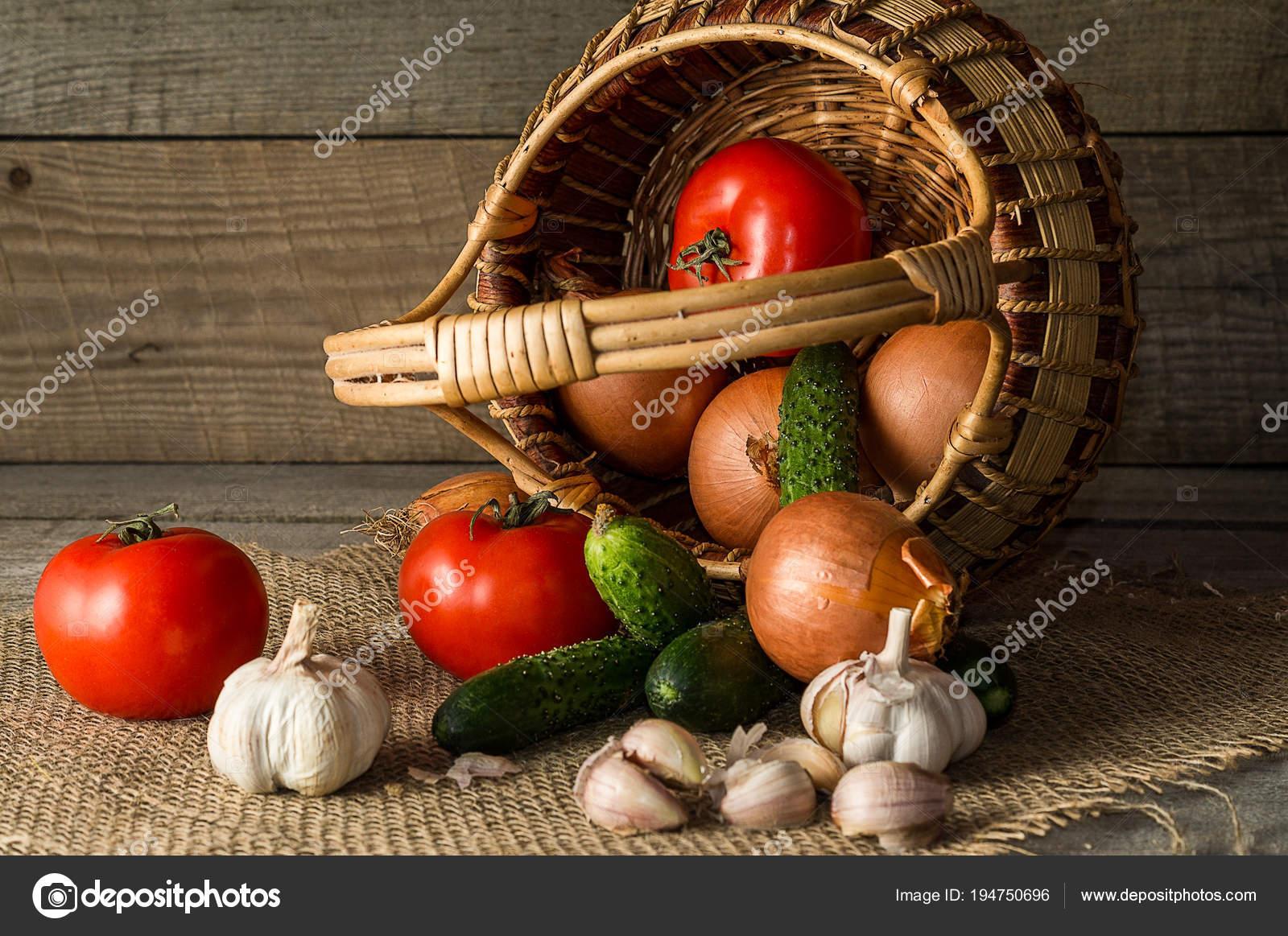 много овощей в корзину против старые деревянные доски и