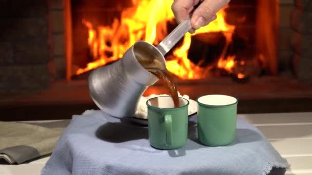 Az asztal forgása, férfi keze forró kávét önt a csészékbe, a hangulatos kandalló előtt, vidéki házban, téli vakáció.