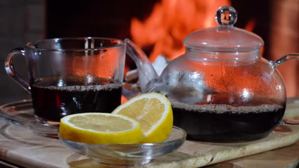 The glass teapot , cup of hot tea and lemon before cozy fireplace, in country house.