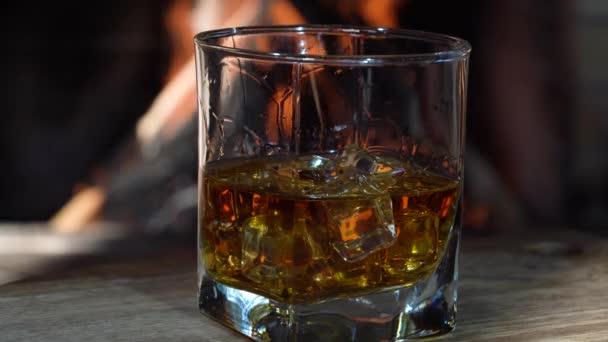 Egy pohár whisky jégkockákkal a hangulatos kandalló előtt, vidéki házban.