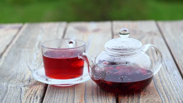 A transparent teapot and a glass cup of hibiscus karkade herbal tea on a wooden table, outdoors on green blurred background.