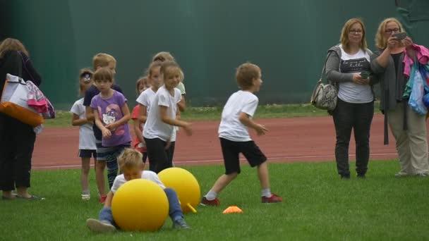 Gyermek játszik egy sárga gumi golyó