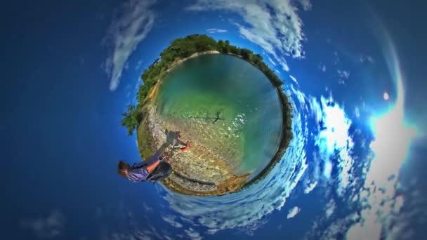 Kis apró Planet 360 fokos ember állandó tengeri nézett hullámzó víz utazik mentén Bank tó meleg napsütéses napon a felhők a Sky túra Opole