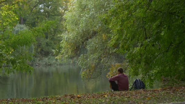 Man Backpacker is Sittng at the Lake Bank Park Forest and Looking at Smooth Water Resting Outdoors Dry Leaves on a Ground Green Trees Autumn Landscape